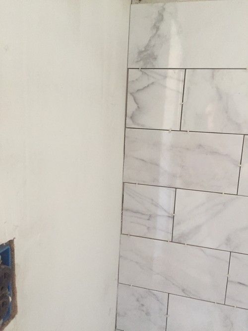 Grout or caulk where tile meets wall?
