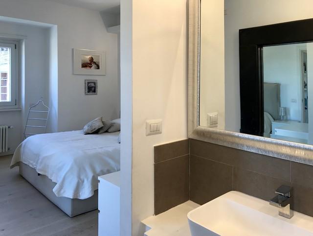 Immagine di una stanza da bagno padronale minimal di medie dimensioni con vasca da incasso, WC sospeso, piastrelle grigie, piastrelle in gres porcellanato, pareti bianche, parquet chiaro, lavabo rettangolare e top in cemento