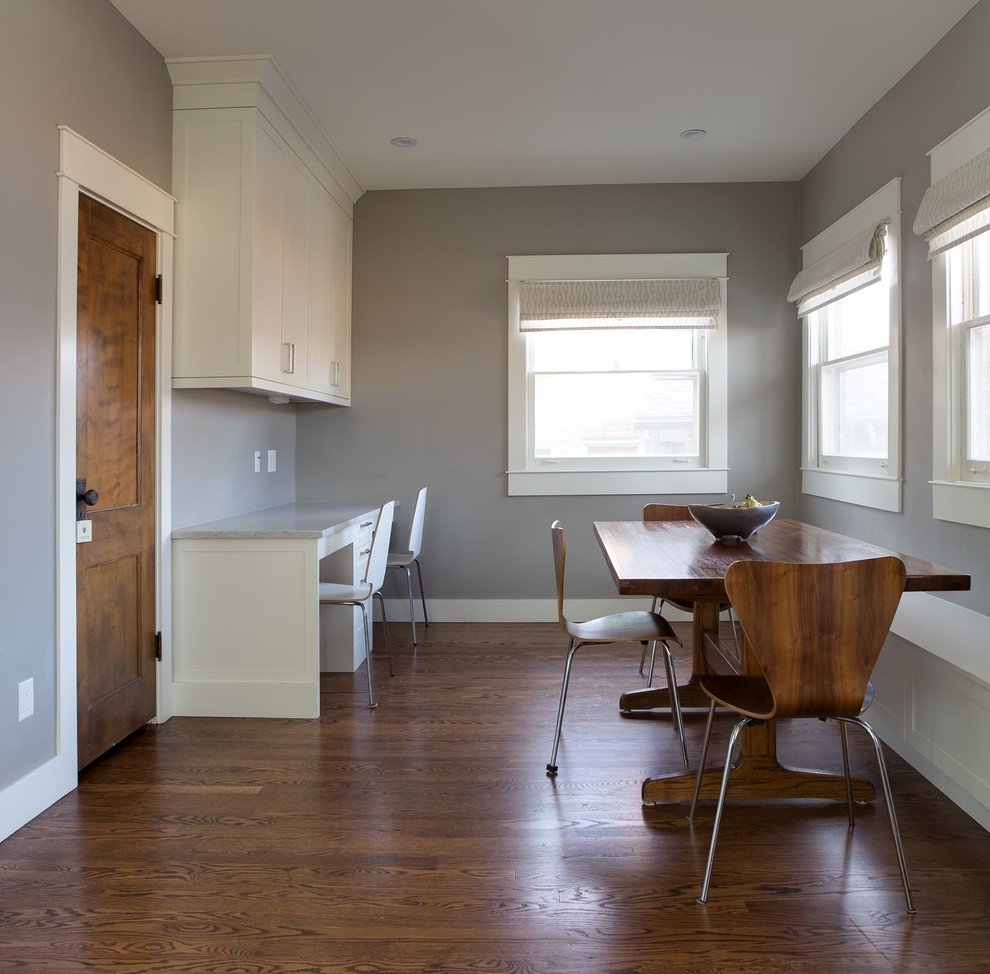 Large trendy dark wood floor and brown floor enclosed dining room photo in Denver with gray walls
