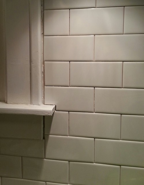 if im using caulk instead of the grout should i use white where the gap is around the window to make it less obvious since the woodwork and tile are both