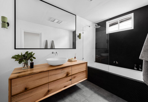 built in bath with black penny tile and timber vanity