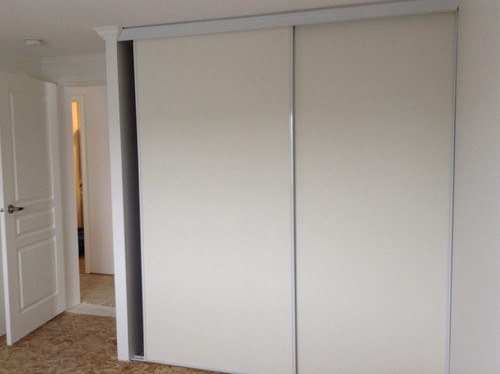 In the spare bedroom  they have put in sliding bypass doors made of a kind  of cheap white board measuring 90 high by 83 wide  Custom doors don t even  come. Crappy closet doors