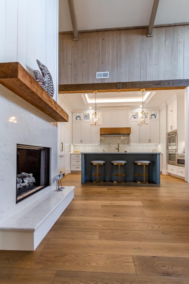Modelo de cocina clásica renovada, pequeña, con fregadero sobremueble, armarios con paneles empotrados, salpicadero multicolor, electrodomésticos de acero inoxidable, una isla, suelo marrón, encimeras blancas y bandeja