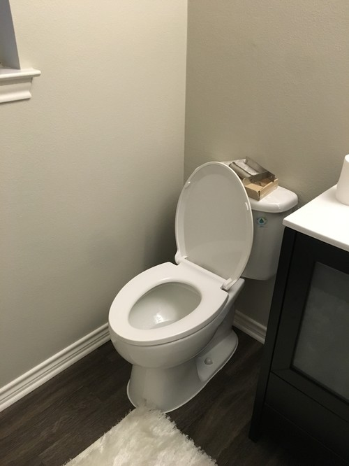 Where do I put the toilet paper holder in my powder room  Or should I just  get a stand  To put it on the wall would be too close to the toilet. Toilet paper