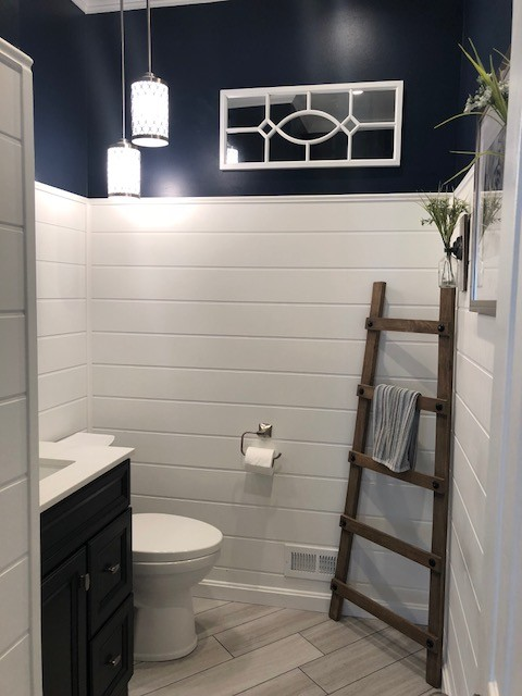 Example of a mid-sized transitional 3/4 porcelain floor and beige floor bathroom design in DC Metro with recessed-panel cabinets, black cabinets, a two-piece toilet, blue walls, an undermount sink, engineered quartz countertops and white countertops