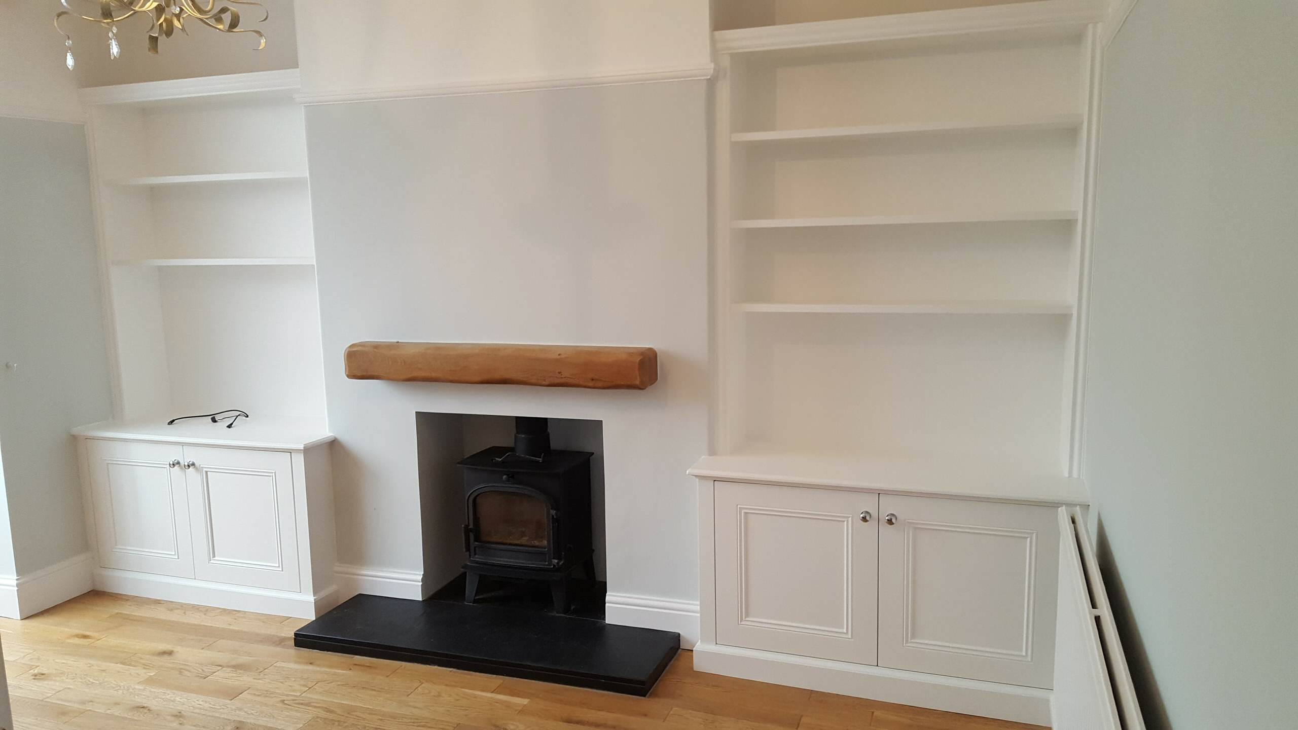 Classic Alcove Units in Off-White Either Side of a Wood Burning Stove