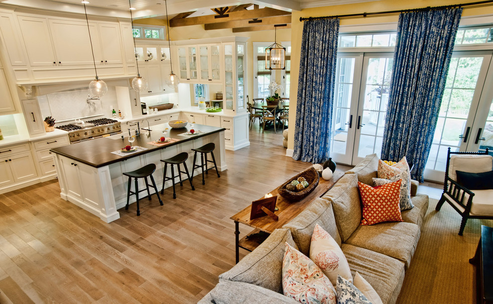 Open concept kitchen - traditional open concept kitchen idea in Other with wood countertops, glass-front cabinets, white cabinets, stainless steel appliances and a farmhouse sink