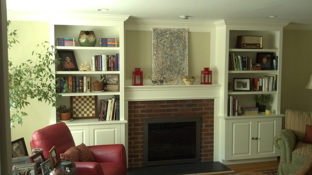 Living room library - mid-sized traditional open concept medium tone wood floor living room library idea in New York with beige walls, a standard fireplace and a brick fireplace