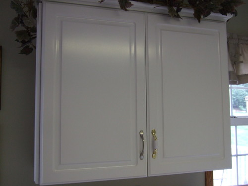 Replace or refinish melamine cabinets in kitchen