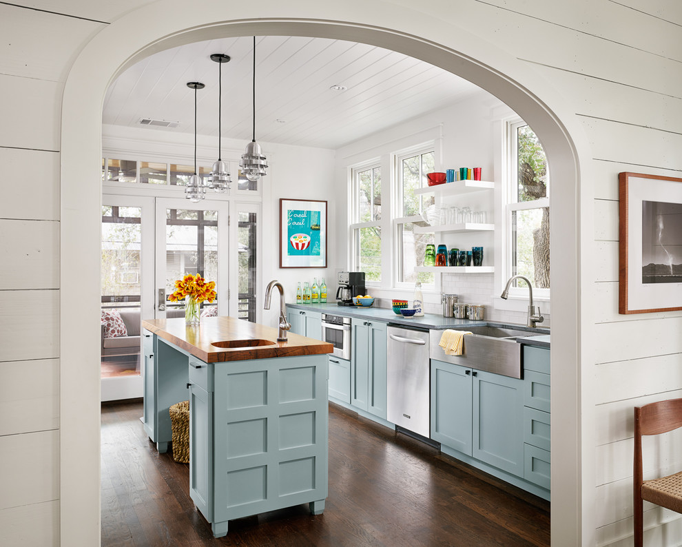 Inspiration for a farmhouse galley enclosed kitchen remodel in Austin with a farmhouse sink, shaker cabinets, blue cabinets, white backsplash and stainless steel appliances