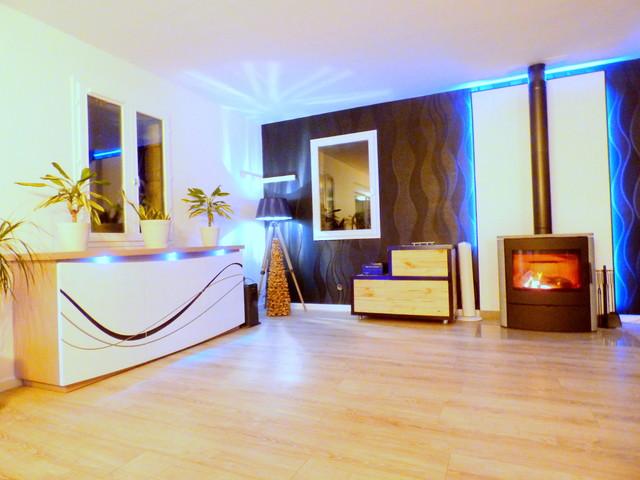 Aménagement d'un très grand salon moderne ouvert avec un mur noir, sol en stratifié, un poêle à bois, un téléviseur indépendant et un sol gris.