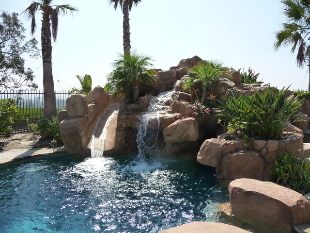 Rock Swimming Pool with Slide, Waterfall and a Table in the ...