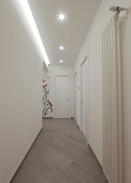 Ispirazione per un ingresso o corridoio minimal di medie dimensioni con pareti bianche, pavimento in gres porcellanato e pavimento grigio