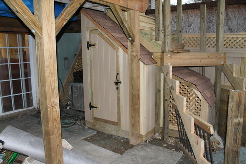 small wood shed built under the stairs of a deck