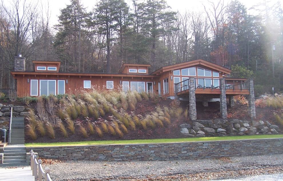 Diseño de fachada de casa marrón, contemporánea, de tamaño medio, de una planta, con revestimiento de madera, tejado a dos aguas y tejado de teja de madera