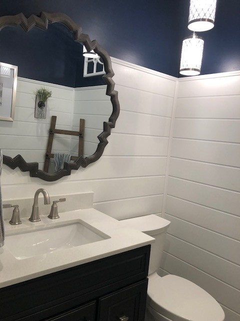 Bathroom - mid-sized transitional 3/4 porcelain floor and beige floor bathroom idea in DC Metro with recessed-panel cabinets, black cabinets, a two-piece toilet, blue walls, an undermount sink, engineered quartz countertops and white countertops