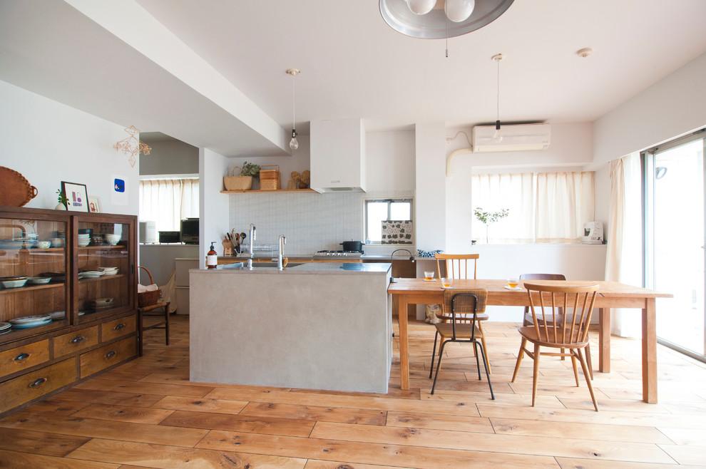 他の地域のII型ラスティックスタイルのダイニングキッチンの画像 (白いキッチンパネル、シルバーの調理設備、無垢フローリング、アイランド1つ)