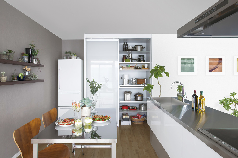 Design ideas for a contemporary single-wall eat-in kitchen in Other with an integrated sink, flat-panel cabinets, white cabinets, stainless steel benchtops, white appliances, medium hardwood floors and a peninsula.