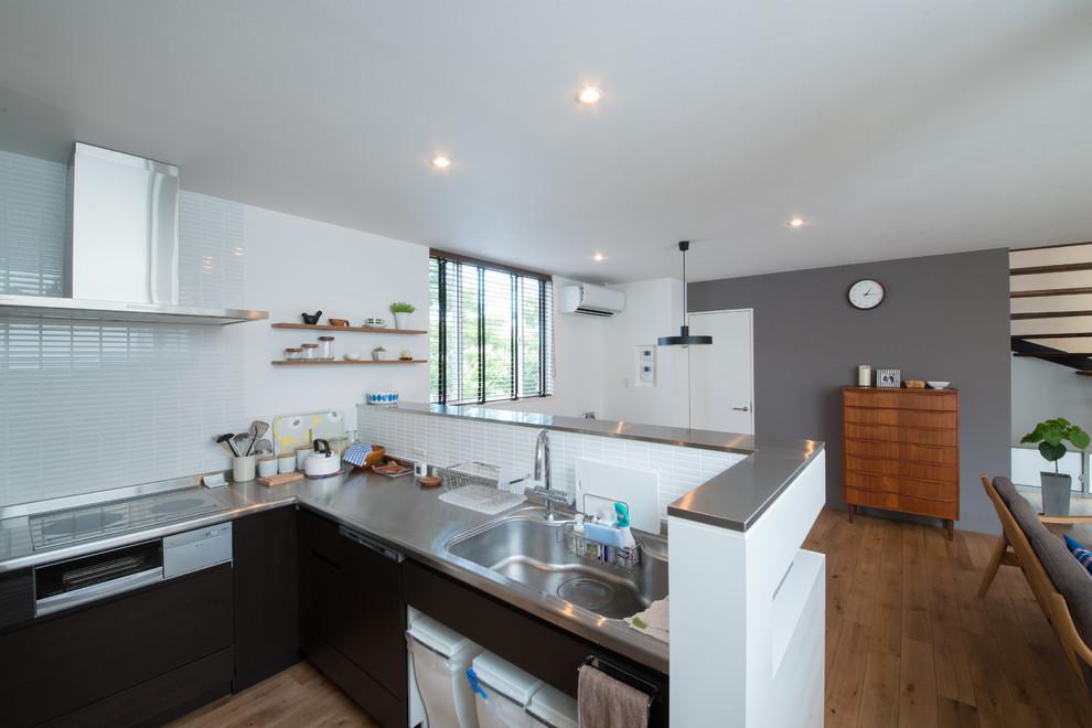 他の地域のL型モダンスタイルのダイニングキッチンの画像 (一体型シンク、フラットパネル扉のキャビネット、濃色木目調キャビネット、ステンレスカウンター、白いキッチンパネル、磁器タイルのキッチンパネル、無垢フローリング)