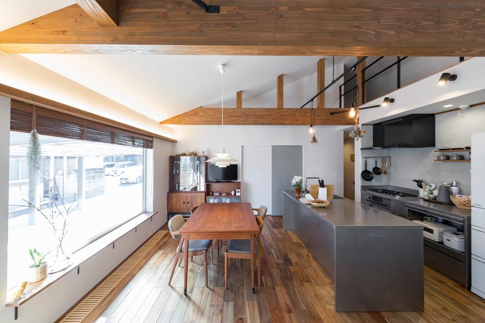 他の地域のインダストリアルスタイルのおしゃれなキッチン (オープンシェルフ、グレーのキャビネット、ステンレスカウンター、シルバーの調理設備、無垢フローリング、茶色い床、グレーのキッチンカウンター) の写真