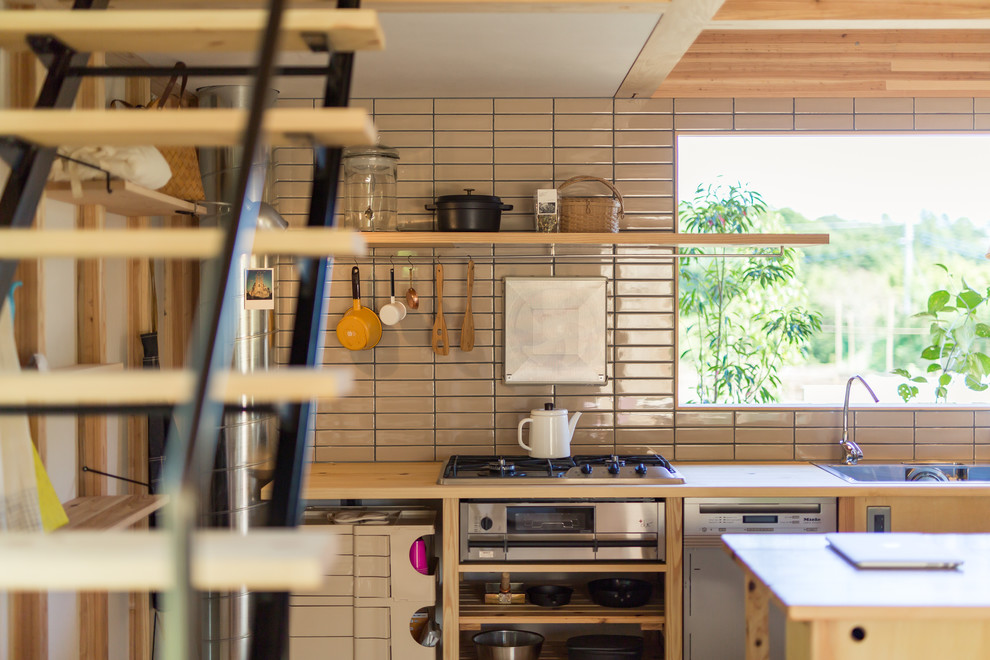 Example of a zen galley medium tone wood floor and beige floor open concept kitchen design in Fukuoka with light wood cabinets, wood countertops, ceramic backsplash, stainless steel appliances, an island, a drop-in sink, flat-panel cabinets, beige countertops and white backsplash