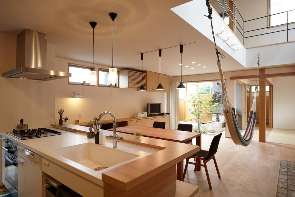 他の地域のアジアンスタイルのおしゃれなキッチン (シルバーの調理設備、一体型シンク、フラットパネル扉のキャビネット、白いキャビネット、淡色無垢フローリング) の写真