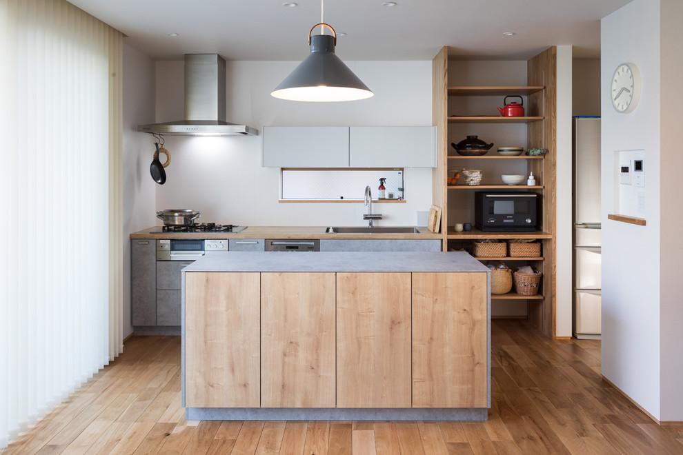 北欧スタイルのおしゃれなアイランドキッチン (シルバーの調理設備、シングルシンク、フラットパネル扉のキャビネット、グレーのキャビネット、木材カウンター、淡色無垢フローリング) の写真