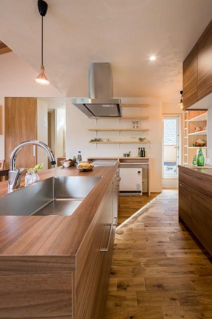 他の地域, のII型アジアンスタイルのキッチンの写真 (シングルシンク、フラットパネル扉のキャビネット、中間色木目調キャビネット、木材カウンター、無垢フローリング、茶色い床)