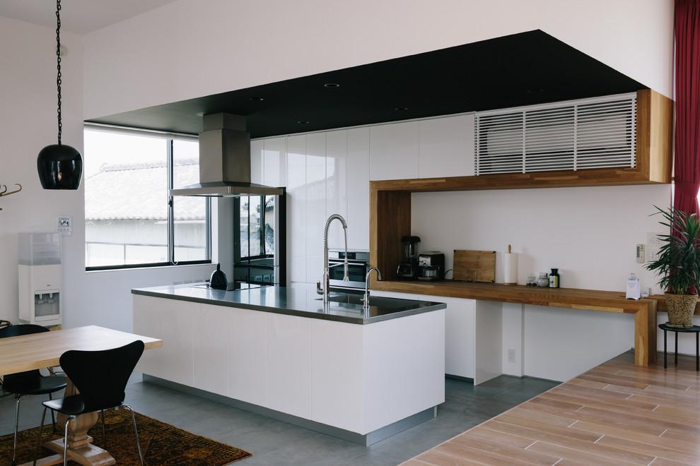 Imagen de cocina asiática con fregadero de un seno, armarios con paneles lisos, puertas de armario blancas, una isla y suelo gris