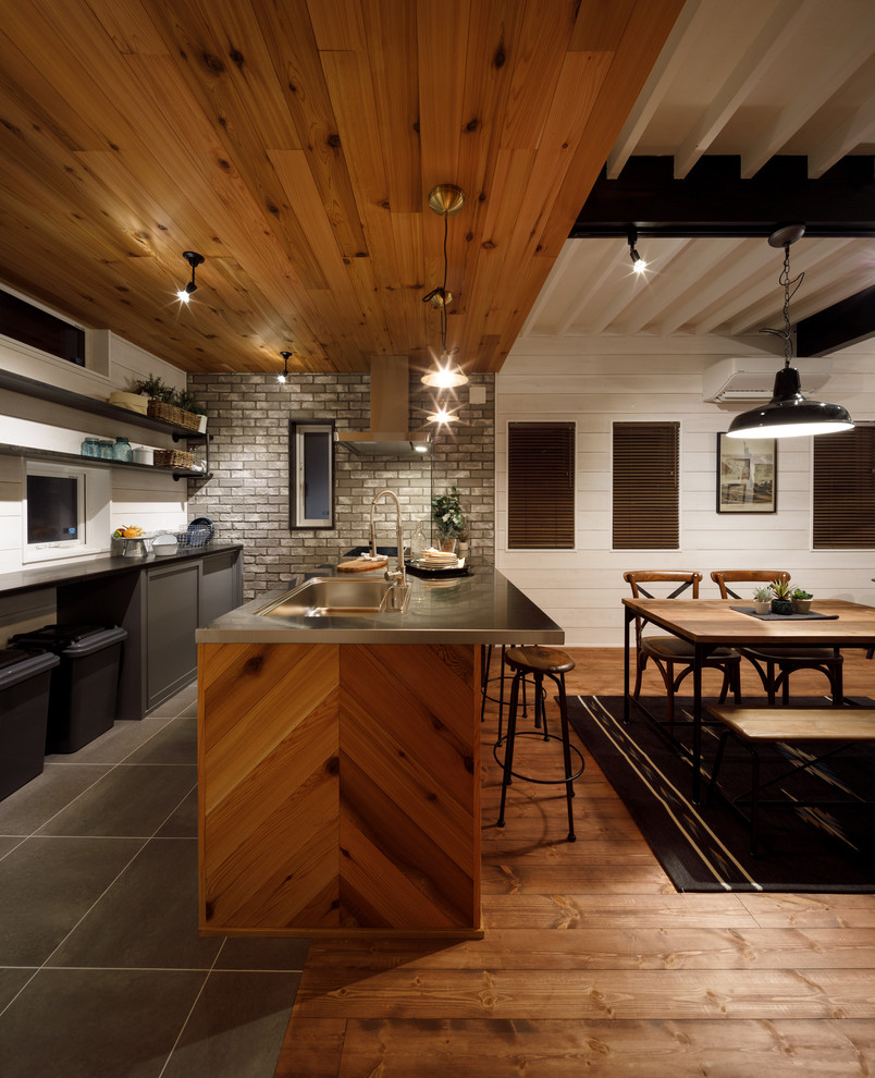 Mid-sized 1960s single-wall open concept kitchen photo in Other with an integrated sink, open cabinets, gray cabinets, stainless steel countertops, gray backsplash, porcelain backsplash and a peninsula