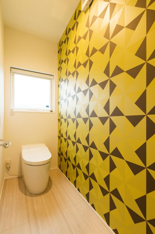 黄色ベースのアクセントクロスを使ったトイレ
