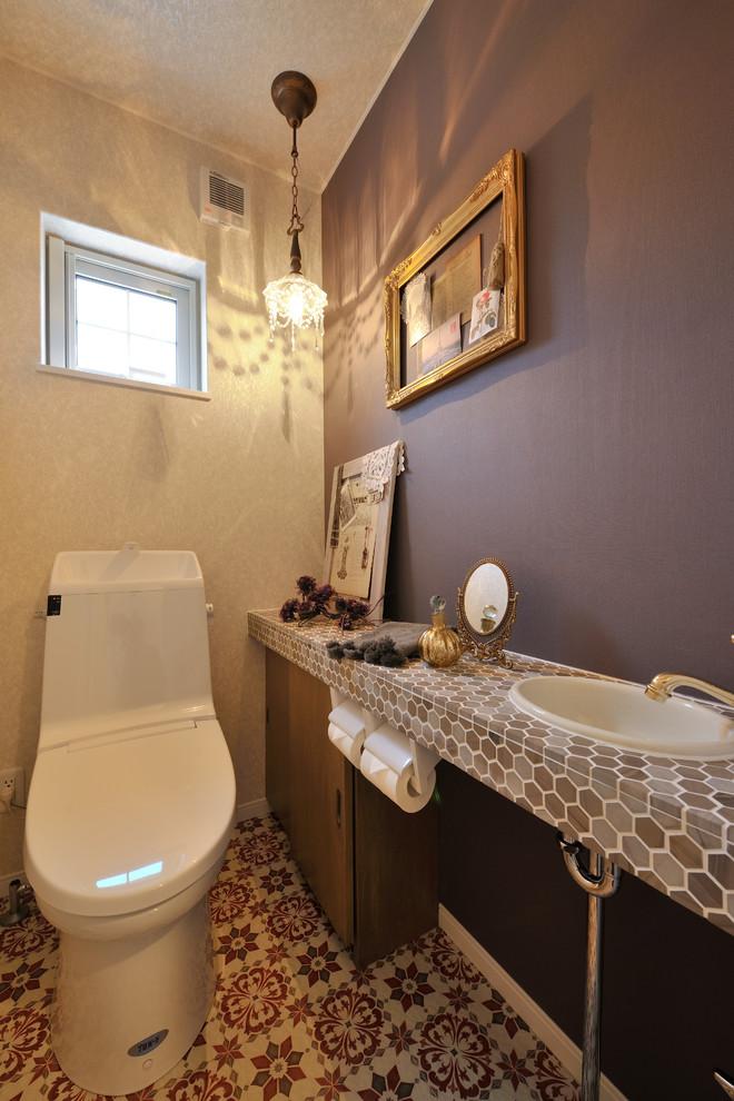 札幌のエクレクティックスタイルのトイレ・洗面所の画像 (フラットパネル扉のキャビネット、中間色木目調キャビネット、グレーのタイル、茶色いタイル、ベージュのタイル、紫の壁、オーバーカウンターシンク、分離型トイレ)