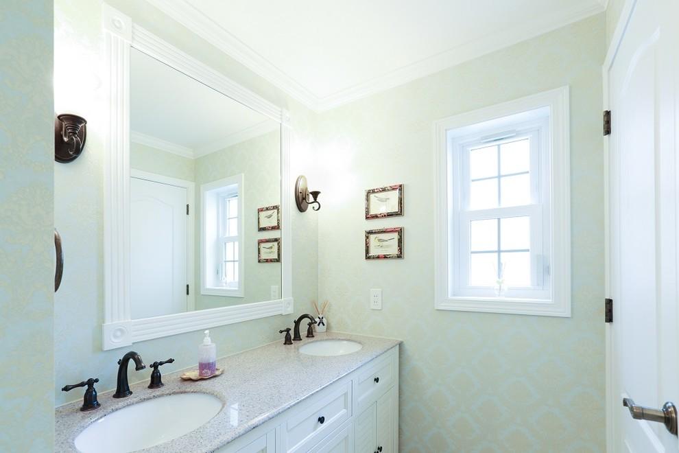 他の地域の広いトラディショナルスタイルのトイレ・洗面所の画像 (家具調キャビネット、白いキャビネット、緑の壁、クッションフロア、オーバーカウンターシンク、人工大理石カウンター、白い床)