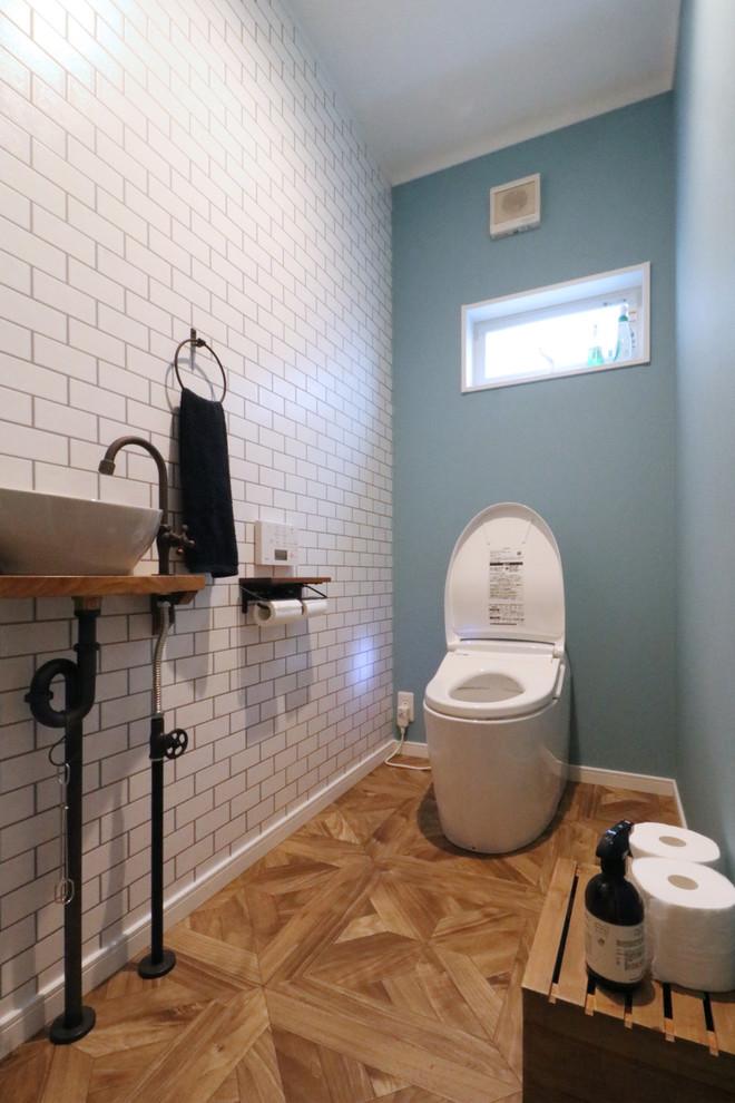 他の地域のカントリー調のトイレ・洗面所の画像 (白いタイル、青い壁、無垢フローリング、ベッセル式洗面器、木製洗面台、茶色い床)
