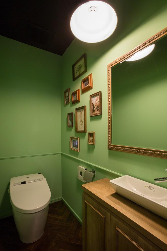 横浜のトランジショナルスタイルのトイレ・洗面所の画像 (緑の壁、ベッセル式洗面器、木製洗面台、分離型トイレ、落し込みパネル扉のキャビネット、淡色木目調キャビネット、ブラウンの洗面カウンター)