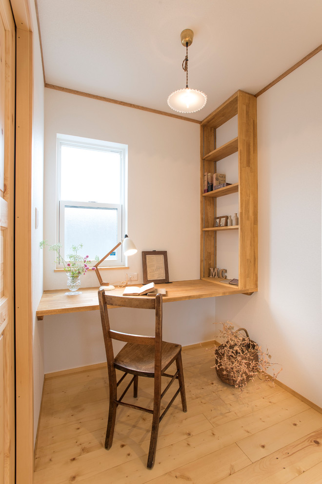 Inspiration for a small asian built-in desk light wood floor and brown floor home office remodel in Other with white walls