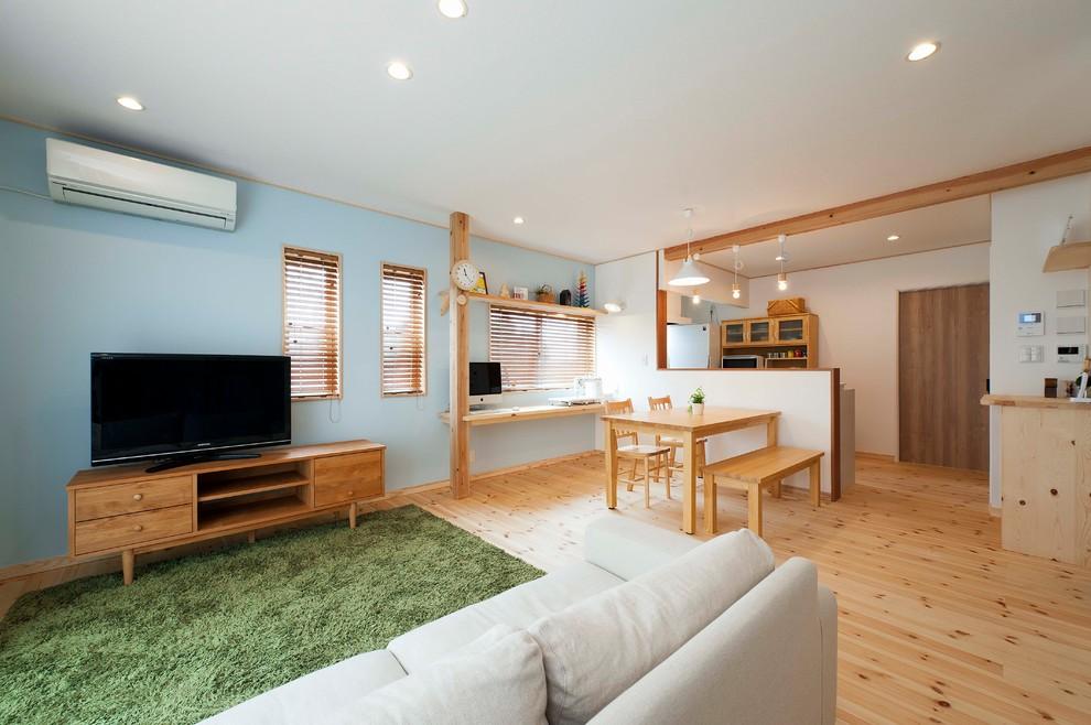 他の地域のアジアンスタイルのリビング・居間の画像 (青い壁、淡色無垢フローリング、据え置き型テレビ、茶色い床)