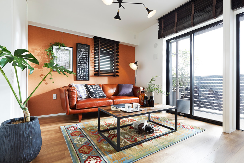 Asian medium tone wood floor living room photo in Tokyo with orange walls, no fireplace and no tv