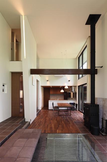 他の地域, の中サイズのモダンスタイルのリビングの写真 (白い壁、濃色無垢フローリング、薪ストーブ、タイルの暖炉まわり、茶色い床)