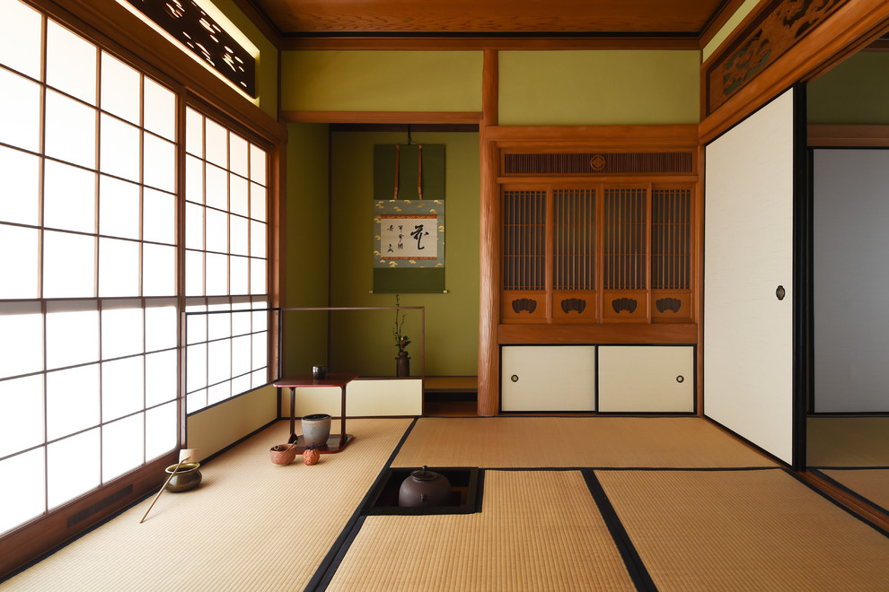 Living room - tatami floor and brown floor living room idea in Other with green walls