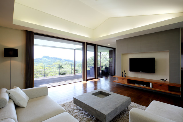 Living room - mid-sized contemporary open concept dark wood floor and brown floor living room idea in Other with beige walls and a wall-mounted tv