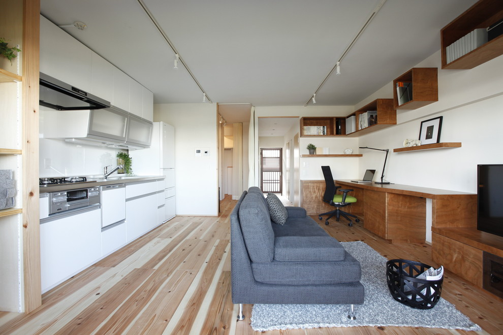 Example of an asian open concept light wood floor living room design in Tokyo with white walls and a tv stand