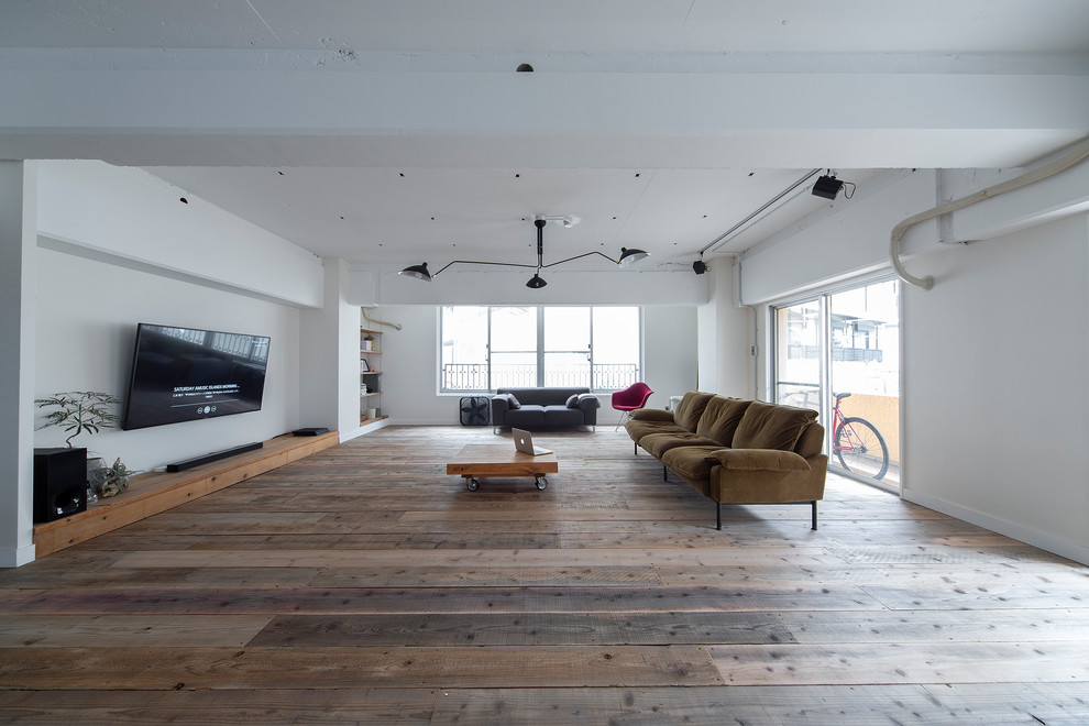 Living room - large industrial open concept medium tone wood floor and brown floor living room idea in Osaka with white walls, no fireplace and a wall-mounted tv