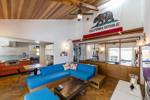 ブルーのソファーでマリンな雰囲気を出したインテリア。壁にかけられたカルフォルニア州の旗が個性的ですね。
