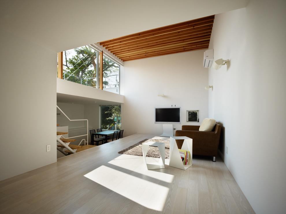 他の地域のアジアンスタイルのリビング・居間の画像 (白い壁、塗装フローリング、据え置き型テレビ、ベージュの床)