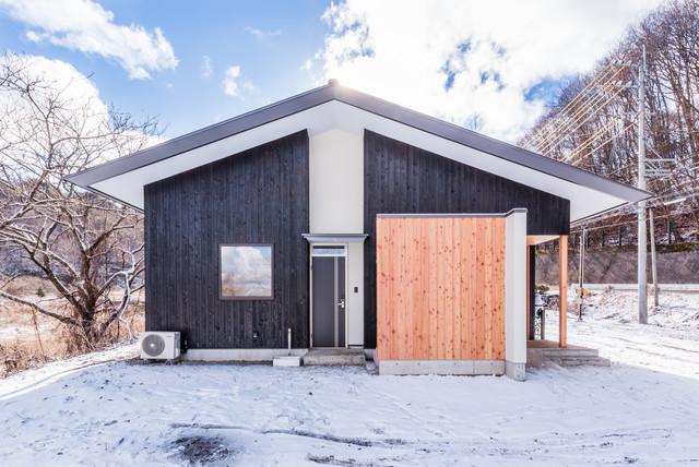 他の地域, のコンテンポラリースタイルの平屋の外観の写真 (木材サイディング、黒い外壁、切妻屋根)