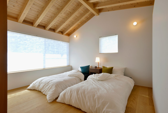 Inspiration for a mid-sized scandinavian guest light wood floor bedroom remodel in Other with white walls