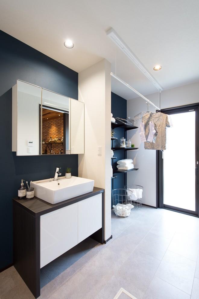 他の地域のコンテンポラリースタイルの浴室・バスルームの画像 (フラットパネル扉のキャビネット、白いキャビネット、黒い壁、ベッセル式洗面器、グレーの床、ブラウンの洗面カウンター)