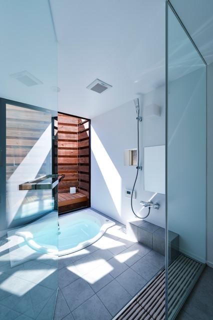 Immagine di una stanza da bagno minimal con vasca ad angolo, doccia aperta, piastrelle grigie, pareti bianche, pavimento in cemento e doccia aperta
