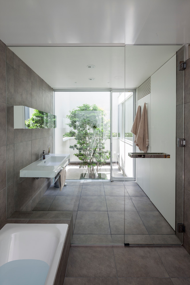 Bathroom - contemporary master gray tile bathroom idea in Yokohama with a wall-mount sink and white walls